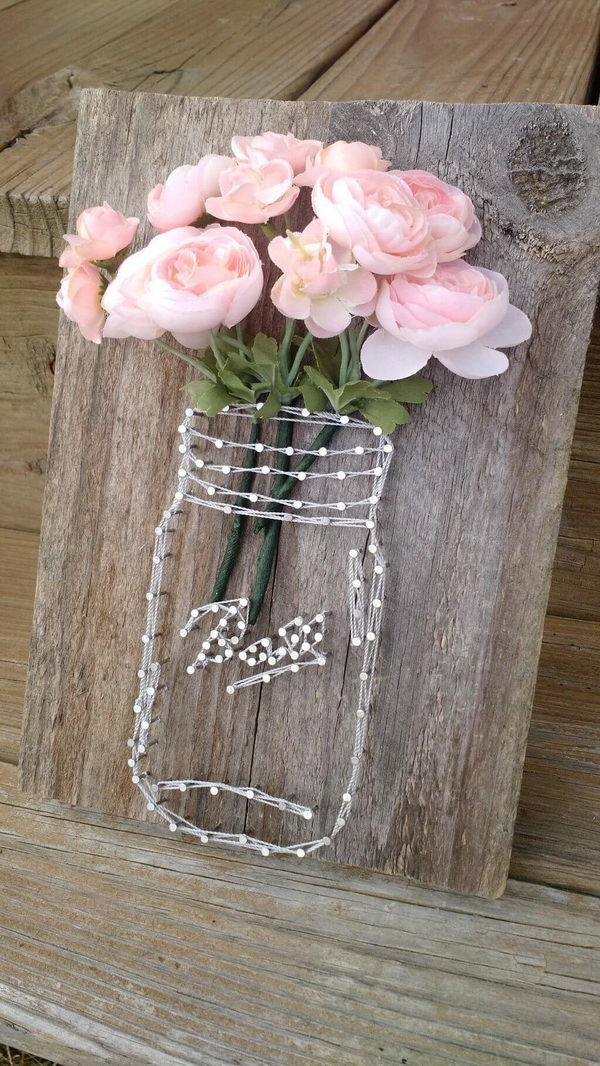 Rustic Mason Jar String Art. Make a unique piece of decor with fake flowers and string! Great Mother's Day Gift and country chic home decor.