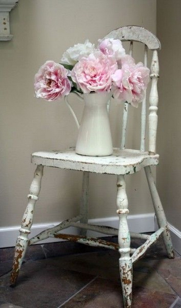 Vintage shabby chic chair with vase and flowerson top for decoration.