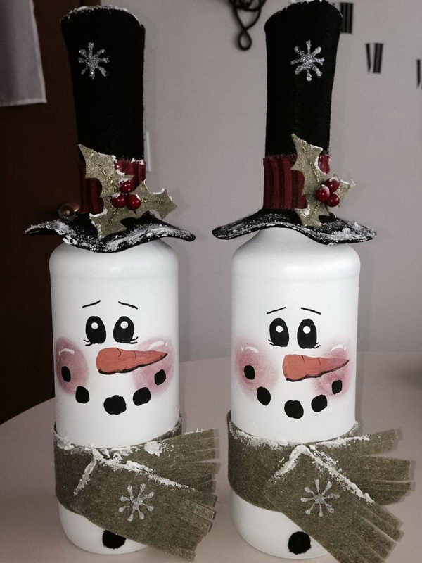 DIY Snowman Painted Wine Bottles. Easily repurpose the emtpy wine bottles with paint into colorful home accents such as these cutest snowman painted wine bottles.