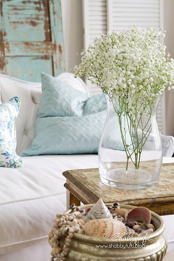 Fresh little flowers on a vase plus some shells and rocks helps decorate the place with coastal vibe.