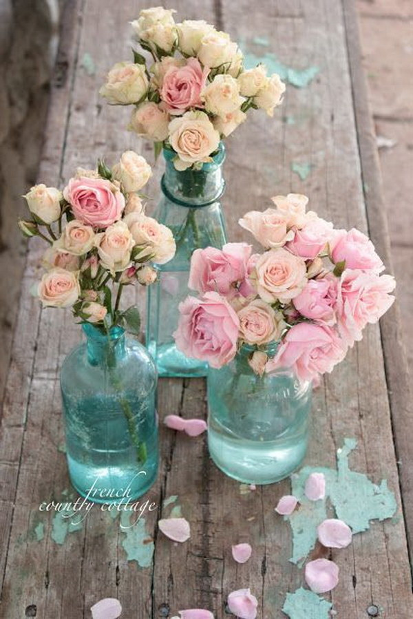 Vintage blue bottles with spray roses inside.