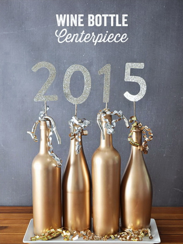 Wine Bottle Centerpiece. Choose four empty wine bottles and spray paint them in gold and top it with the numbers of your graduation year. Super easy and fun and stunning table centerpiece for your graduation party decor!